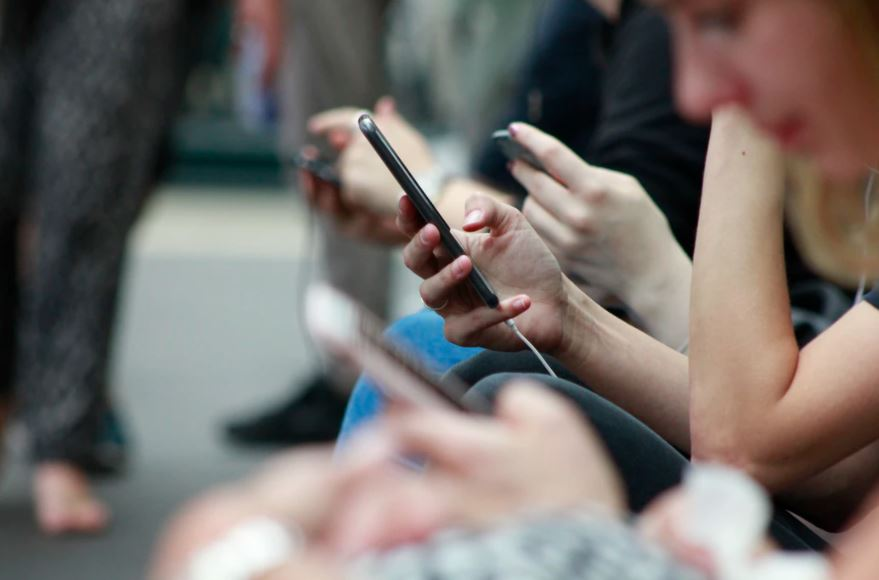 Mobile phone users sitting on park bench