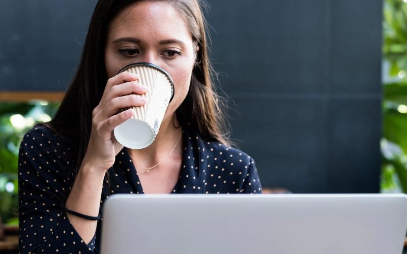 woman drinking coffee browsing laptop